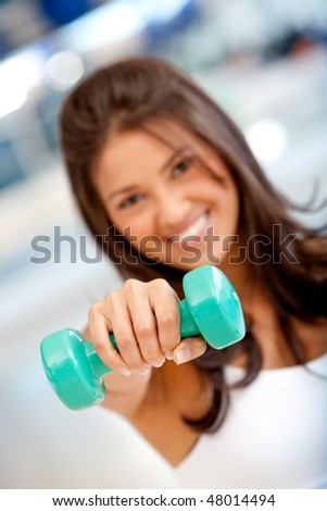 beautiful gym woman holding a freeweight in front of her face