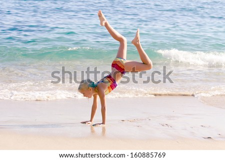 Beautiful gymnastic little girl doing her exercises on the beach - stock photo