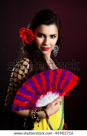 Beautiful gypsy woman with fan and attractive look - stock photo