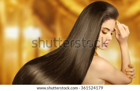 Beautiful Hair. Beauty brunette woman with luxurious long hair over golden background. Makeup. Girl Model girl with Healthy Hair. Smooth shiny straight hairstyle. Manicured nails. Hair cosmetics. - stock photo
