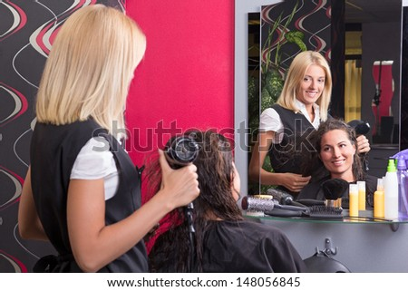 beautiful hairdresser with hairdryer and smiling customer in beauty salon - stock photo