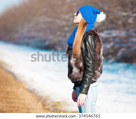 Beautiful haired sexy woman, dressed blue jeans, hat and scarf, fur jacket, sunglasses. Has long hair and elegant slim body, walking to road, go in hitch-hiking. Portrait urban city. Real lady.