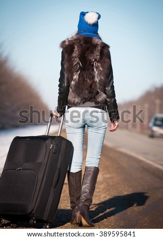 Beautiful haired sexy woman, dressed blue jeans, leather boots, fur jacket, sunglasses. Has long hair, legs and elegant slim body, walking to road and holding suitcase.   - stock photo