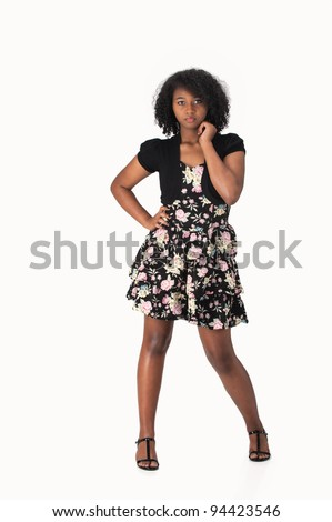 Beautiful Haitian African American teenage girl wearing a floral dress and posing against a white background. - stock photo