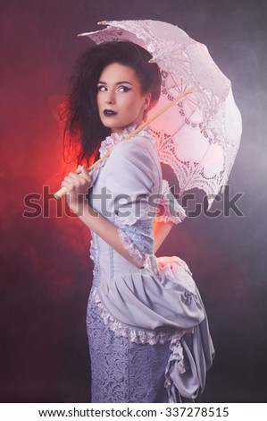 Beautiful Halloween vampire woman aristocrat with lace-parasol - stock photo