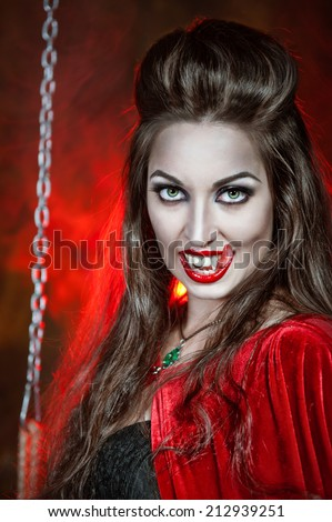 Beautiful halloween vampire woman with long tongue - stock photo