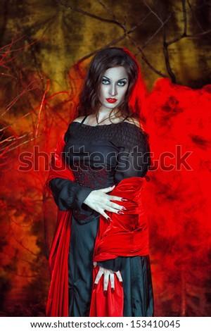 Beautiful halloween witch in the smoke - stock photo