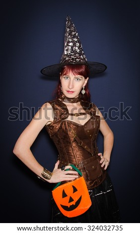 Beautiful halloween witch with pumpkin bag. - stock photo