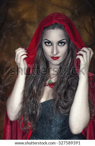 Beautiful halloween woman with long hair in red cloak  - stock photo