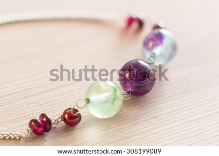 Beautiful hand made amethyst and garnet vintage beads macro shoot on a wooden background  - stock photo