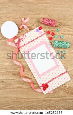 Beautiful hand made post card and scrapbooking elements, on wooden table - stock photo