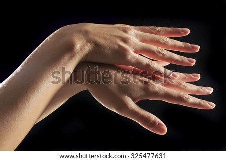 beautiful hand of a young lady  over black background  - stock photo