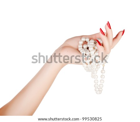 beautiful hand of a young woman with red manicure holding white pearl necklace on white background - stock photo