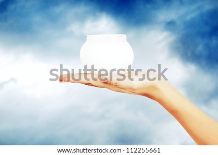 Beautiful hand of the girl with a cream on a sky - stock photo