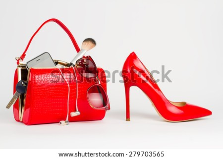 Beautiful handbag with women's accessories stands near the red shoes. - stock photo