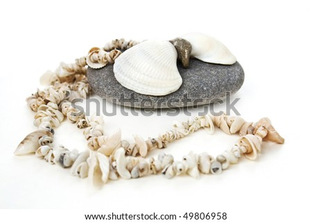 Beautiful handmade shell's necklace on pebble over white background - stock photo