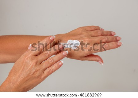 Beautiful hands of middle aged woman are using cream, on a gray background