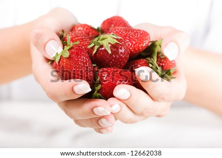 Beautiful hands with French manicure and fresh strawberry. Soft-focused, low DOF - stock photo