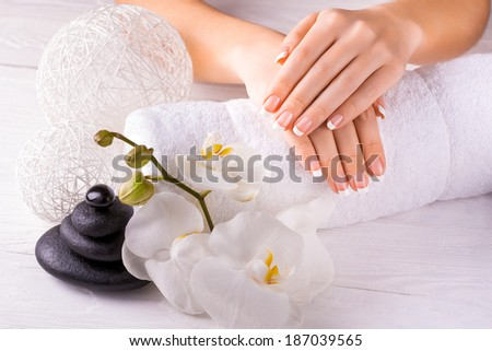 Beautiful hands with manicure and orchid flower - stock photo