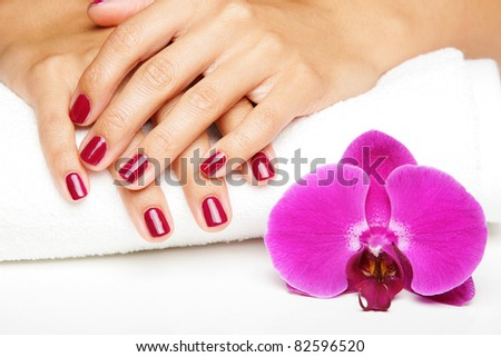 Beautiful hands with manicure and purple orchid flowers - stock photo