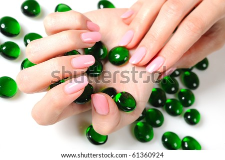 Beautiful hands with perfect nail pink manicure and green decorative stones. isolated on white background - stock photo