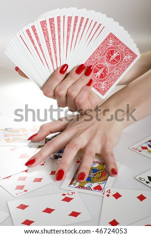 Beautiful hands with perfect red manicure holding a deck of playing cards - stock photo