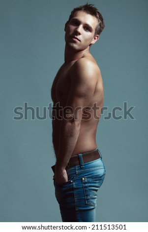 Beautiful (handsome) muscular male model with nice abs in blue jeans with leather belt posing over blue (gray) background. Hands in pockets. Urban style. Fashion studio portrait - stock photo