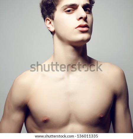 Beautiful (handsome) muscular male model with nice body posing over light-gray background. Close up. Emotive studio portrait. - stock photo