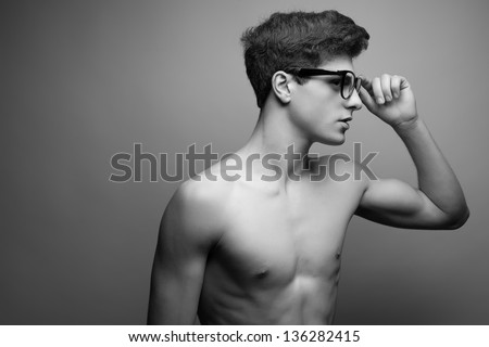 Beautiful (handsome) muscular male model with nice body wearing trendy glasses and posing over light-gray background. Hipster style. Copy-space. Black and white (monochrome) studio portrait.