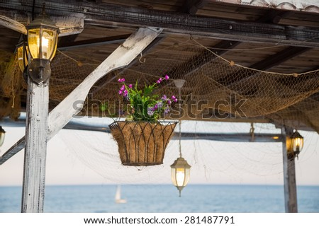 Beautiful hanging basket with artificial flowers hooked on a wooden shelter on the sea shore, surrounded by glowing vintage lamps.  - stock photo
