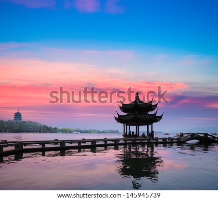 beautiful hangzhou in sunset, ancient pavilion silhouette on the west lake,China - stock photo