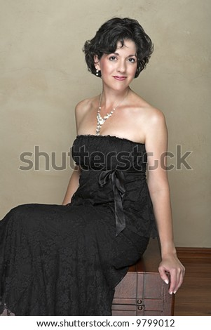 Beautiful happy adult woman with black curly hair and soft natural make-up, wearing black evening or cocktail dress and fashion pearl accessories