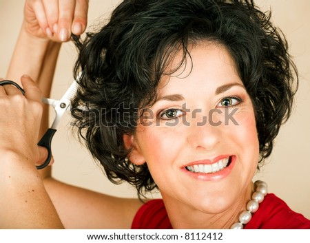 Beautiful happy adult woman  with black curly hair cutting her hair with scissors. Visible skin texture with pores and wrinkles - stock photo
