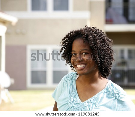 Beautiful happy African-American girl in front of modern apartment (condo) building - stock photo