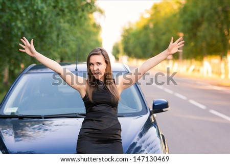 Beautiful happy and excited business woman in her car - stock photo