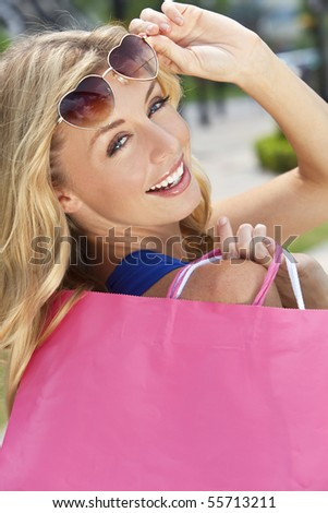 Beautiful, happy and fashionable young blond woman with heart shaped sunglasses and colorful shopping bags over her shoulder.