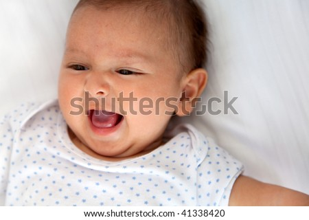 Beautiful happy baby lying doing grimaces indoors