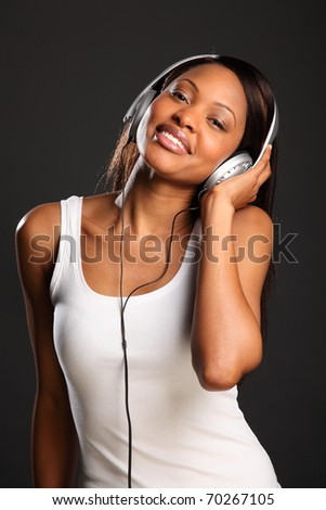Beautiful happy black woman enjoying music - stock photo