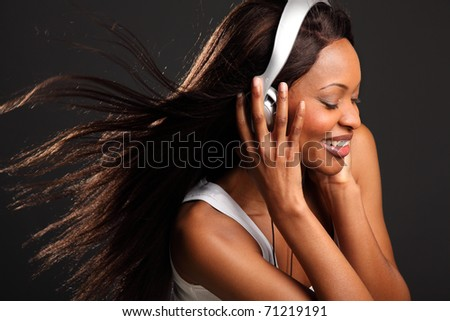 Beautiful happy black woman listening to music - stock photo
