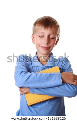 Beautiful happy blond boy in a blue t-shirt embracing a big yellow book and dreaming with his eyes shut (isolated on white background) - stock photo