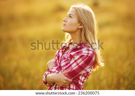 Beautiful happy blond girl in shirt looking up - stock photo
