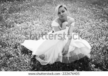 Beautiful happy blonde woman in the park on a warm summer day.Portrait of young lovely woman in spring flowers.Beautiful spring girl in blooming tree.Beautiful woman with white flowering tree - stock photo