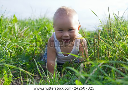 beautiful happy boy playing in grass