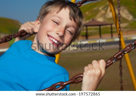 Beautiful happy boy swinging on a playground in a sunny park and laughing  - stock photo