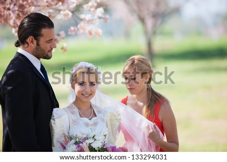 Beautiful happy bride and groom shot in the cherry blossoms with their bridesmaid  springtime - stock photo