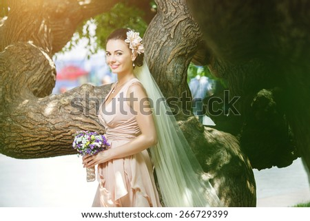 beautiful happy bride in beige dress smiling standing among green trees in sunlight - stock photo