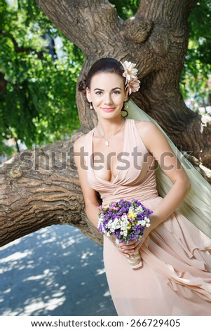 beautiful happy bride in beige dress with plunging neckline smiling standing among green trees - stock photo