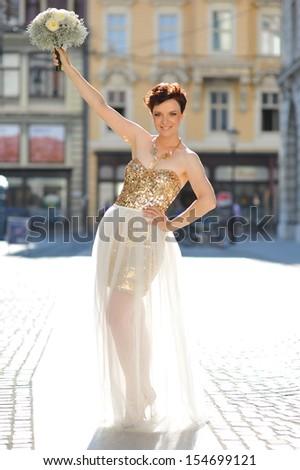 Beautiful happy bride in gold dress - stock photo