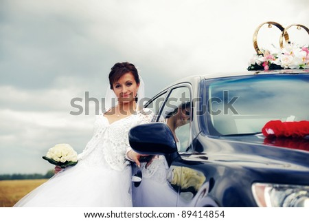 Beautiful happy bride near wedding car outdoors