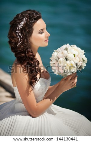 beautiful happy bride with wedding flowers bouquet with wedding hairstyle bright makeup and diamond hairpin jewelry in hair in love. Gorgeous bride rich girl in wedding dress waiting for groom. - stock photo